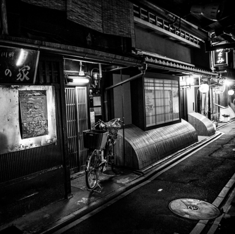 black and white photo of a bicycle parked outside a building in a street in old town kyoto