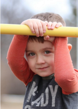 Photo of a little kid holding onto a yellow bar, arms framing the face. Photo by Melanie Young.