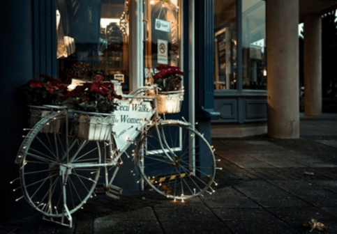bike sitting outside a shop front with fairy lights on the wheels