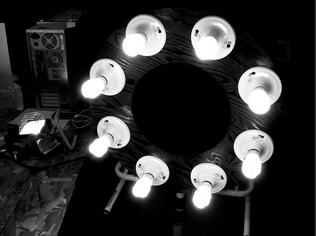 black and white photo of light rig which is a disk with several lightbulbs in it.