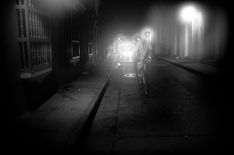 People riding bicycles in the dark wearing headlamps. Black and white photo