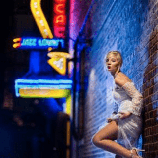 a woman leaning against a wall at night with neon signs in the background