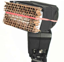a flash with corrugated cardboard strapped to it using a rubber band
