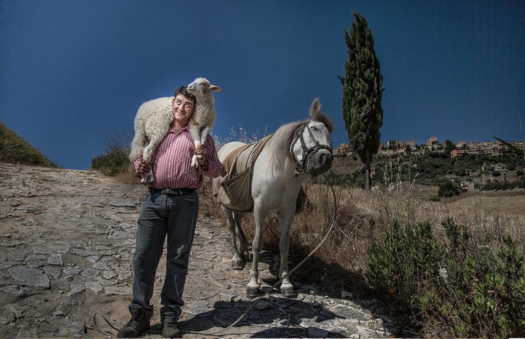 man with sheep on shoulders standing in front of donkey
