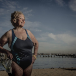 older woman in a swim suit standing in front of a pier