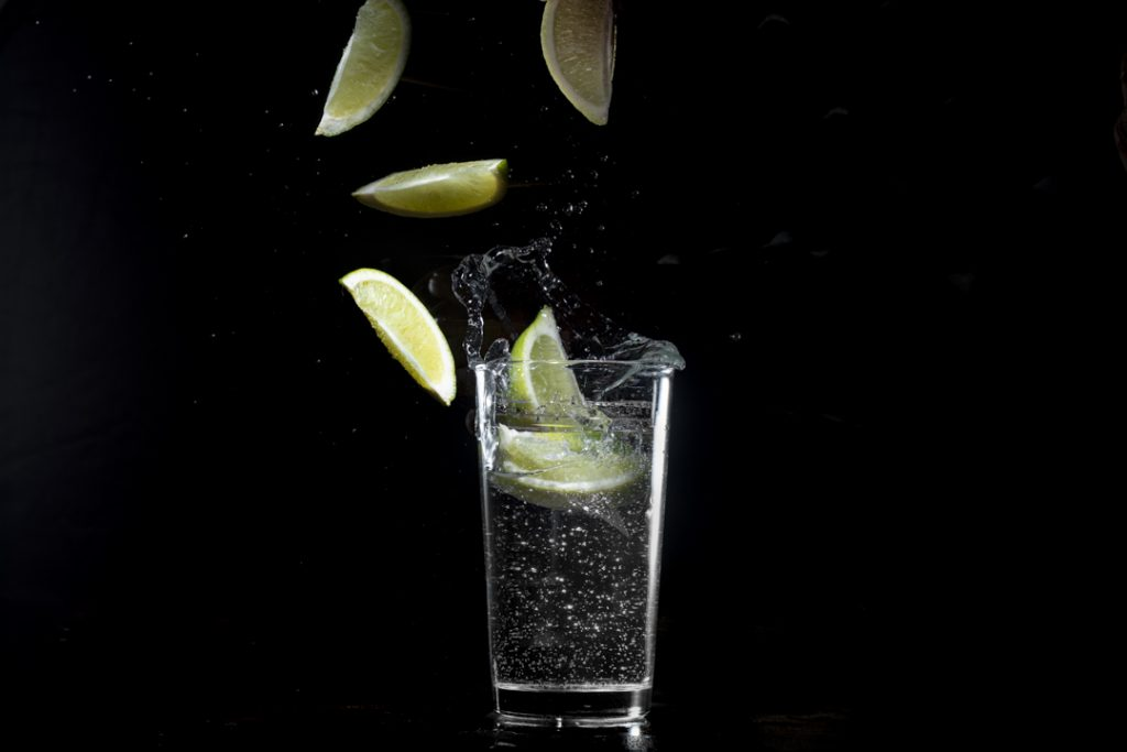 A glass of water against a black background with lemon wedges being dropped into it. You can see the splash and the bubbled in the glass as well as water droplets.